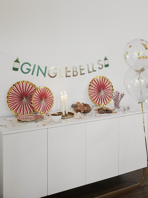 Zbliżenie na białą komodę w salonie udekorowaną na przyjęcie świąteczne z papierowymi ozdobami i girlandą