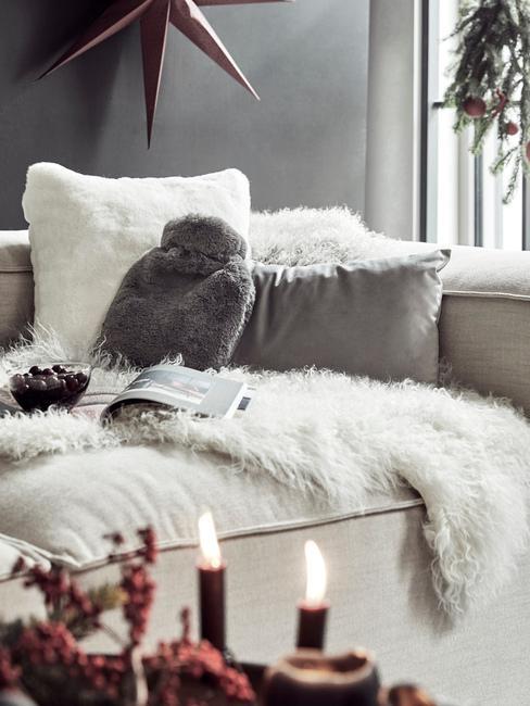 Wnętrze szarego salonu z białą sofą z poduszkami i kocem