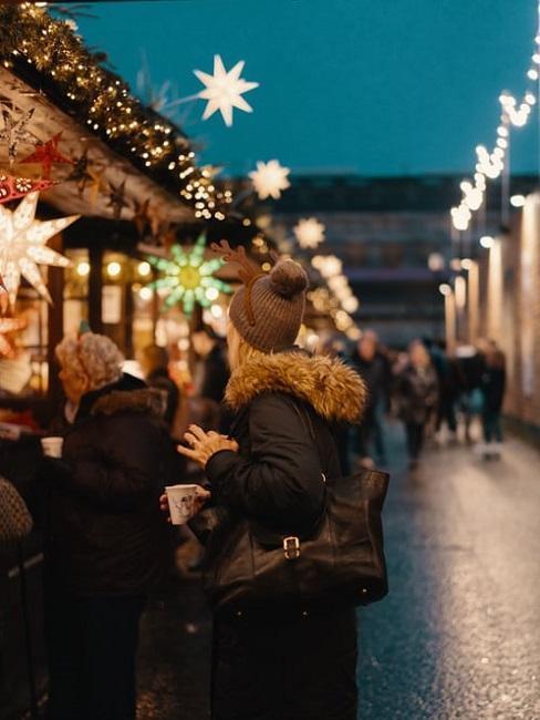 Kobieta stojąca przy jarmarku świątecznym