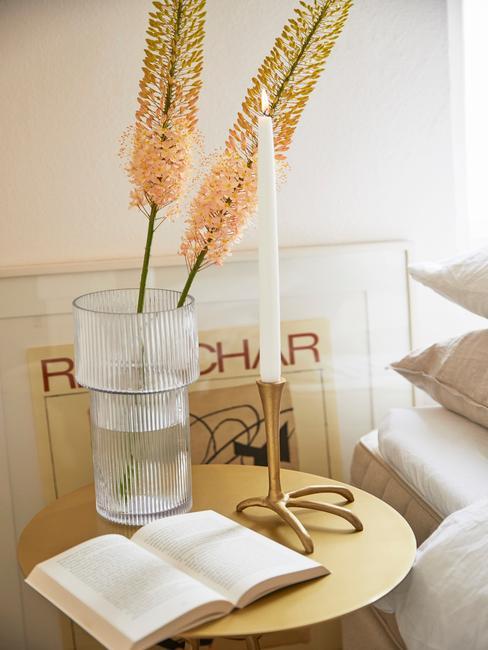 Zbliżenie na stolik z wazonem z kwiatami, świecą i książką