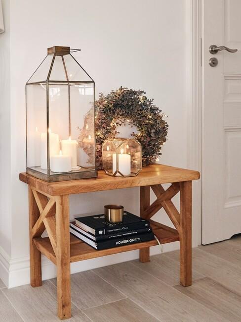 Zbliżenie na drewnianą, otwartą szafkę z latarenką, wieńcem oraz świeczkami