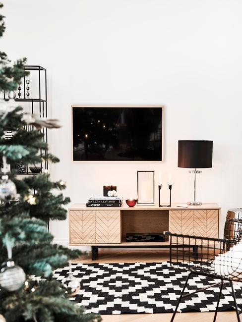 Wnętrze salou z telewizorem, konsolą oraz udekorowaną choinką