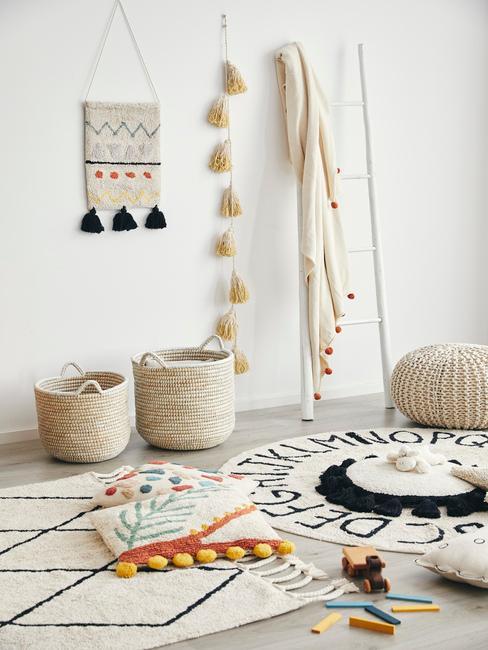 Białe wnętrze boho z koszykami, białą drabiną z kocem, dwoma dywanami i pufem