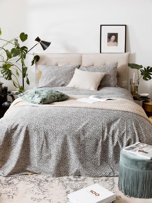 Wnętrze sypialni z podwójnym łożkiem, szarej pościeli, poduszkach, roślinami oraz pufem