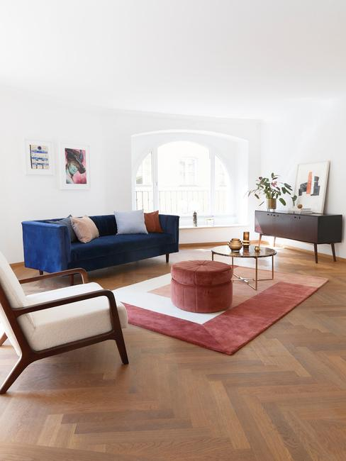 Wnętrze salonu etno z granatową sofą, białym fotelem, różowym pufem i dywanem