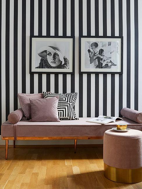 Różowy szezlong z aksamitu na tle tapety w czarno-białe pasy