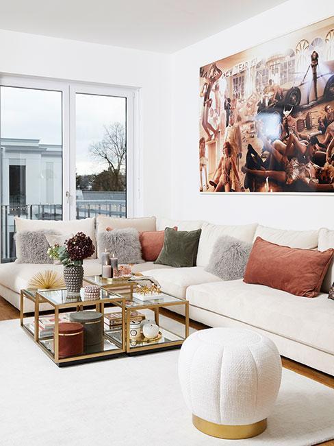 Beżowa sofa narożna z poduszkami w jesiennych kolorach i szklanym stolikiem kawowym ze złotymi zdobieniami