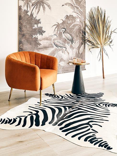 Pomaraćczowy fotel z aksamitu na dywanie w zebrę