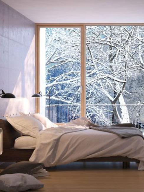 sypialnia w lofcie z dużym oknem z ośnieżonym drzewem na dworze