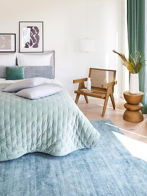 Sypialnia w stylu boho z narzutą w kolorze szałwii i drewnianymi meblami