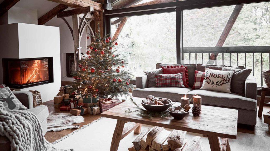 Przytulny salon w stylu hygge z kominkiem, ubraną choinką, szarą sofą z poduszkami oraz drewnianym stolikiem kawowym