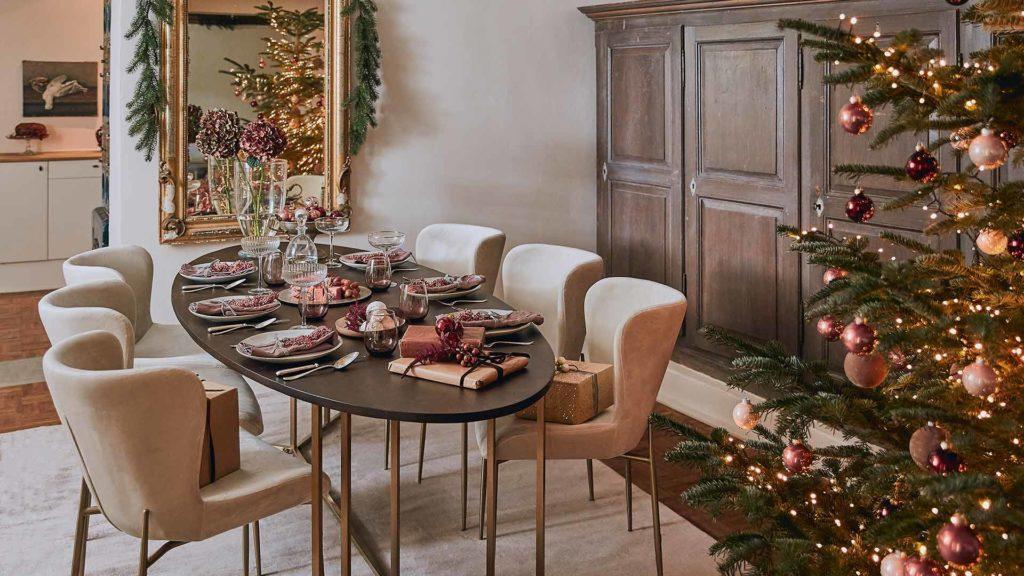 Wnętrze jadalni z dużym, zastawionym stołem, beżowymi krzesłami, drewnianą komoda oraz choinką