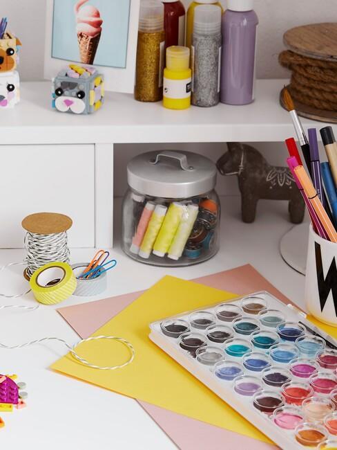 Fragment białego biurka dziecięcego z przyborami do malowania