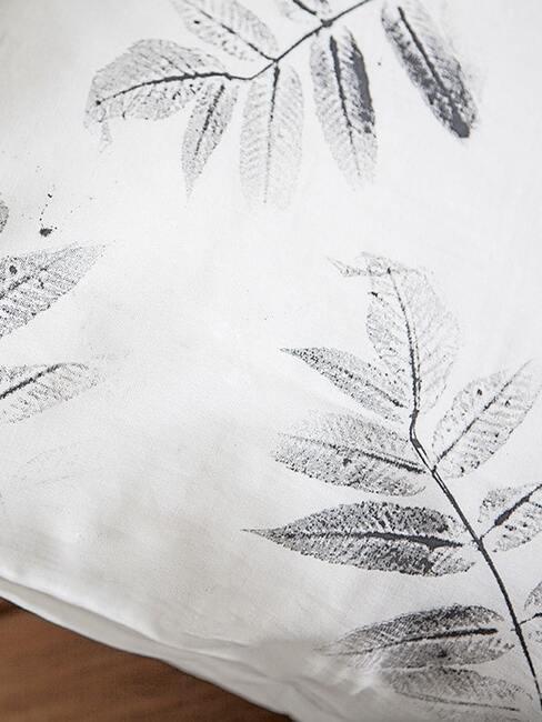 Zbliżenie na białą pościel udekorowaną stemplami do tkanin DIY