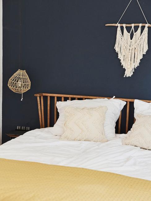Ciemnoniebieska sypialnia w łożkiem w stylu boho oraz makramą nad nim