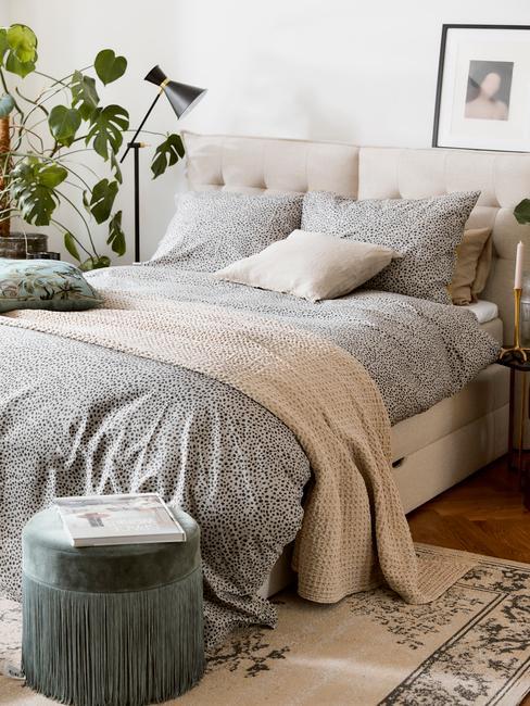 Zbliżenie na łóżko w sypialni z pościelom, poduszkami, kocem