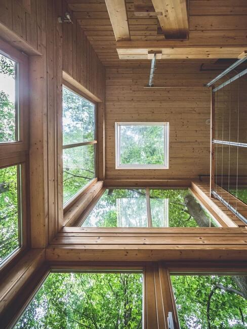 Przeszklone wnętrze drewnianego domku z oknami