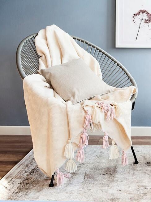 Zbliżenie na fotel w stylu boho, na którym jest ułożony koc z frędzlami oraz szara poduszka