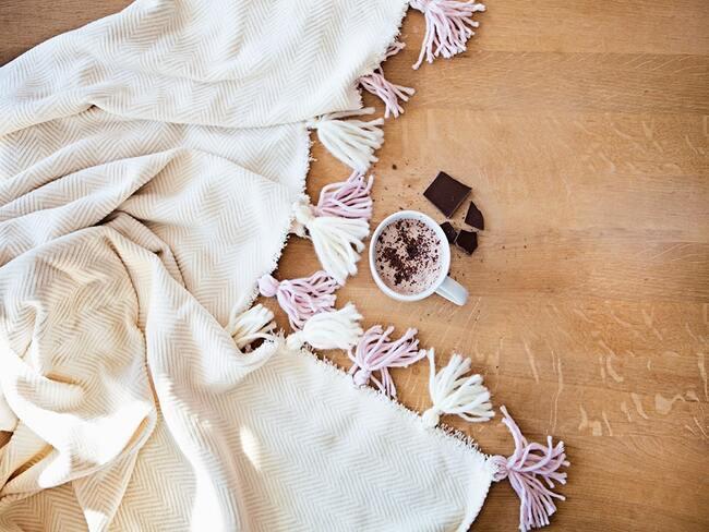 zbliżenie na biały koc z własnoręcznie zrobionymi frędzlami oraz kubek kakao