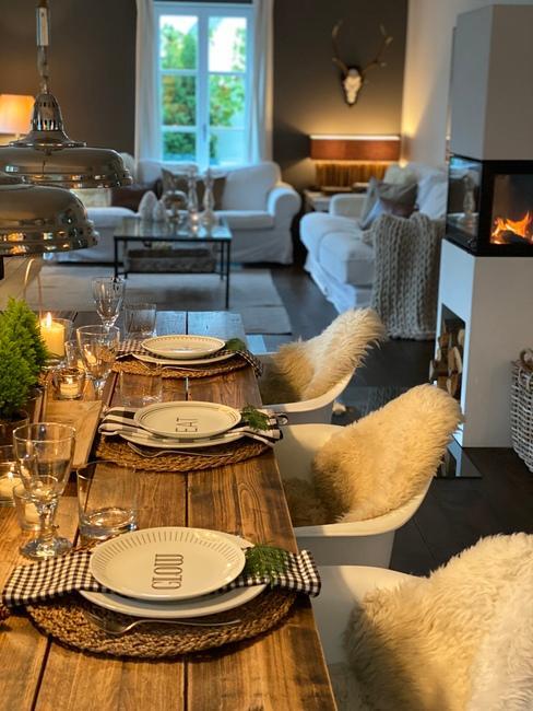 Wnętrze jadalni z dużym, drewnianym stołem oraz świąteczną zastawą