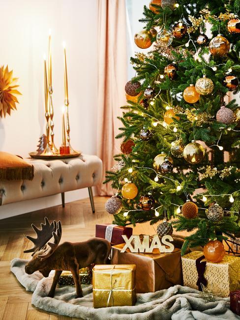 Świątecznie udekorowana choinka we wnętrzu pod którą znajdują się prezenty oraz ławka