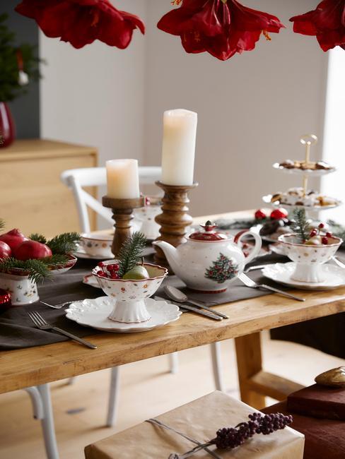 Zbliżenie na drewniany stół z zastawą oraz świecami