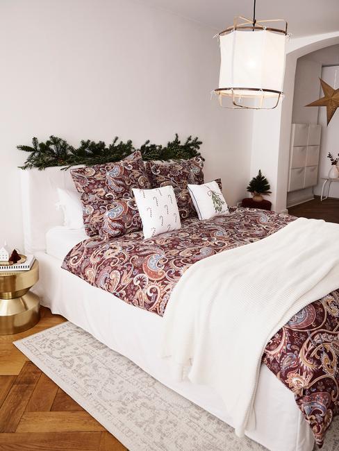 Łóżko w sypialni ze świąteczną pościelą i poduszkami