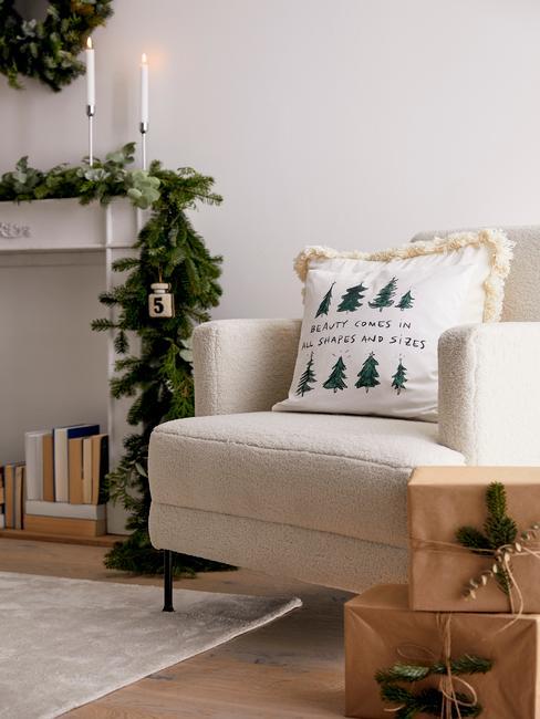 Biały fotel w salonie oraz kominika udekorowanego girlandą