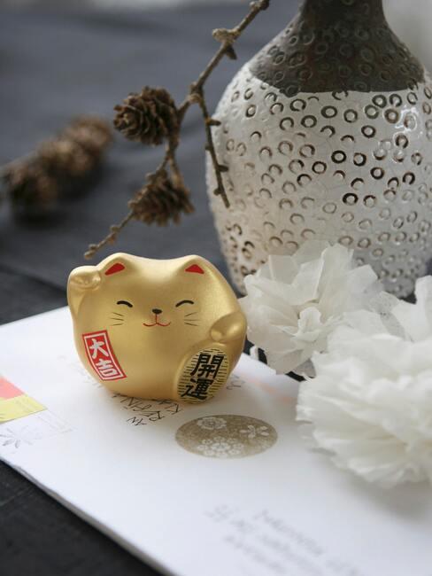 Złoty kot Maneki Neko na białym stoliczku, obok wazonu