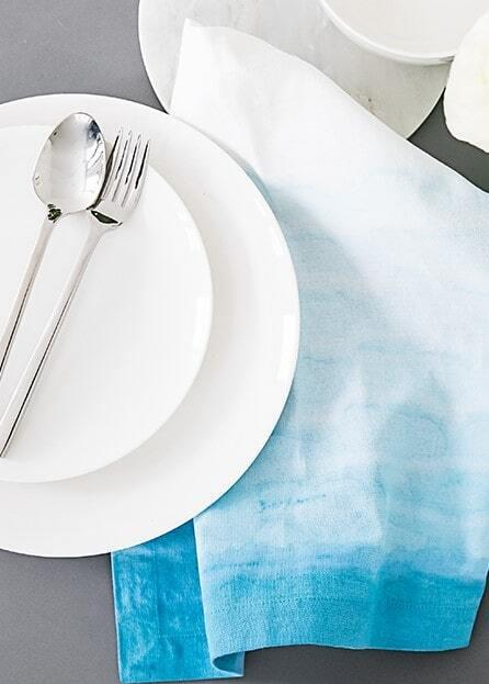 Biały zestaw talerzy oraz srebrne sztućce ułożone obok serwetki ombre