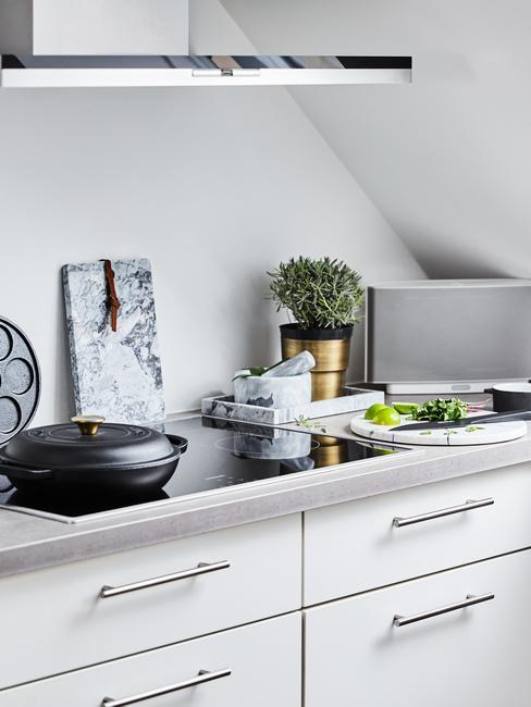 Kuchnia na poddaszu z szafkami o białych frontach, sprzętami kuchennymi i doniczką ziół