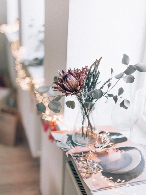 suszona protea w szklanym wazonie z gałązkami eukaliptusa na parapcie