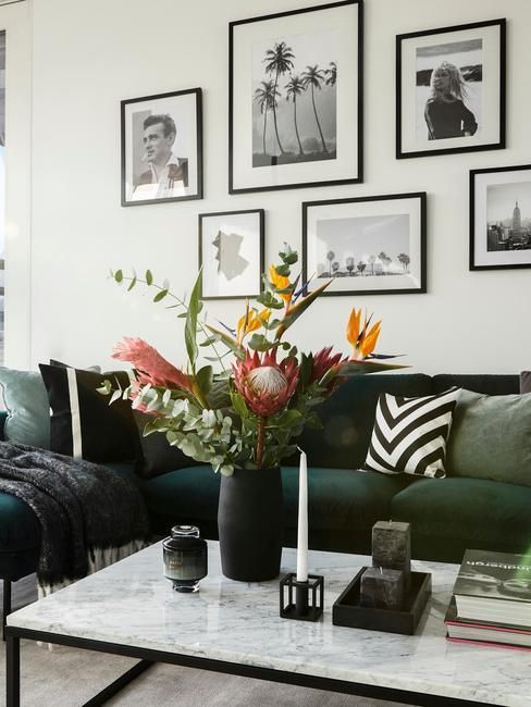 wnętrze salonu z ciemnozieloną sofą, marmurowym stolikiem kawowym z czarnym wazonem z kwiatami