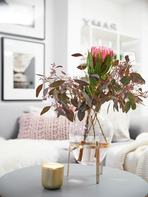 Zbliżenie na szklany wazon z bukietem kwiatów, w któym znajduje się protea