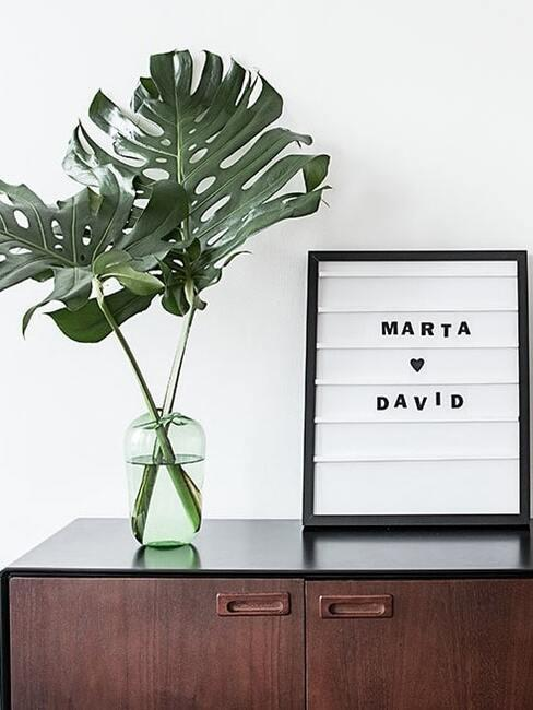 Własnoręcznie zrobiona tablica z literami ustawiona na ciemnej, drewnianej komodzie obok wazonu z monstera