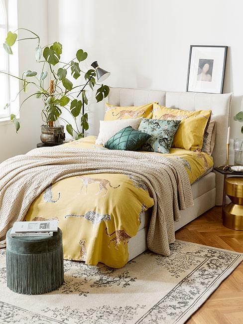 Sypialnia z żółtą pościelą z motywem zwierzęcem obok dużej monstery