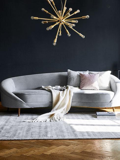 Szara sofa nerka na tle ciemnej ściany