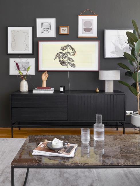 Fragment salonu z czarną ścianą, z gelarią obrazów, telewizorem nad czarną komodą z dekoracjami