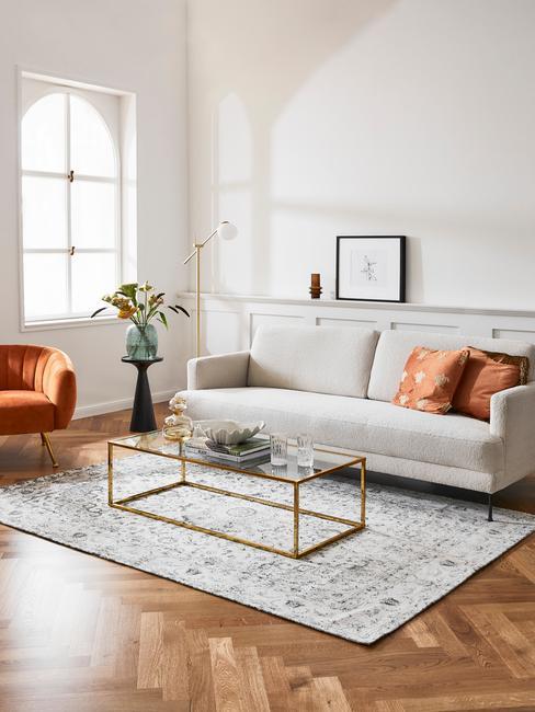wnętrze jasnego salonu z szarą sofą, pomarańczowym fotelem, metalowym stolikiem kawowym oraz szarym dywanem