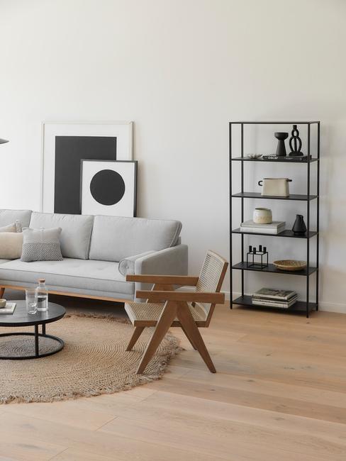 Biały salon z czarną, metalową otwarta półką z dekoracjami, szarą sofą, drewnianym fotelem oraz dywanem