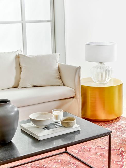 Zbliżenie na białą sofę, okrągłu stolik z lampką, stolik kawowy z dekoracją