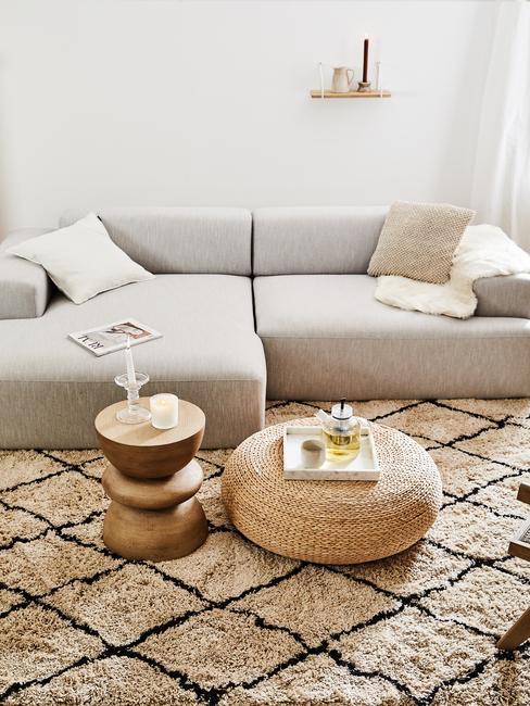 Zbliżenie na jasną sofę z poduszkami, beżowo-czarnym dywanem, jutowym pudem i małym stoliczkiem