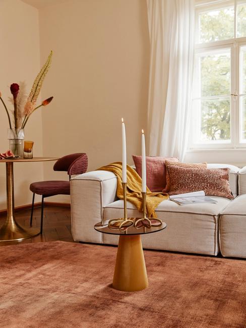 Wnętrze salonu z szampańskimi ścianami, białą sofą z tekstyliami i dwoma stoliczkami
