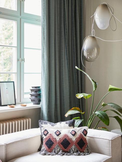 wnętrze salonu z sofą, rośliną i srebrnym żyrandolem