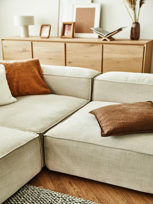 zbliżenie na beżową sodą z poduszkami w salonie z drewnianą, dużą komodą