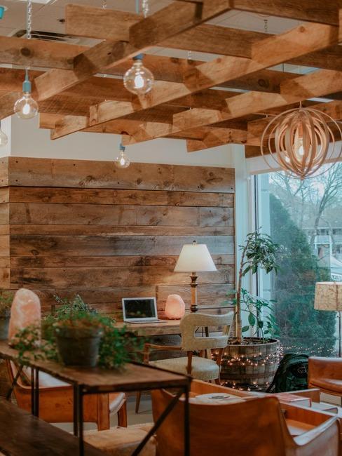 Nowoczesne biurko z elementami drewna na ścianie, biurkami, roślinami, lampami oraz dekoracjami