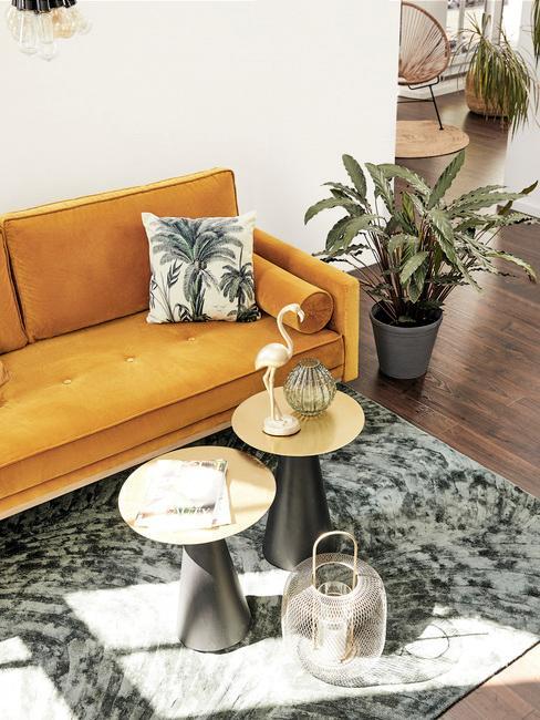 Wnętrza salonu retro z żółtą sofą, stolickami, dywanem, poduszką z motywem roślinnym oraz rośliną