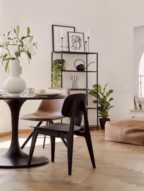 Zbliżenie na czarny stół i krzesło oraz metalową, otwartą półkę z roślinami