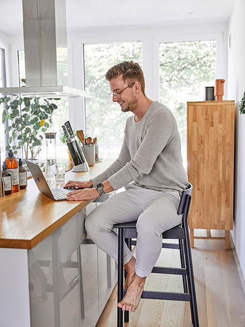 Męóczyzna pracujący na laptopie w kuchni