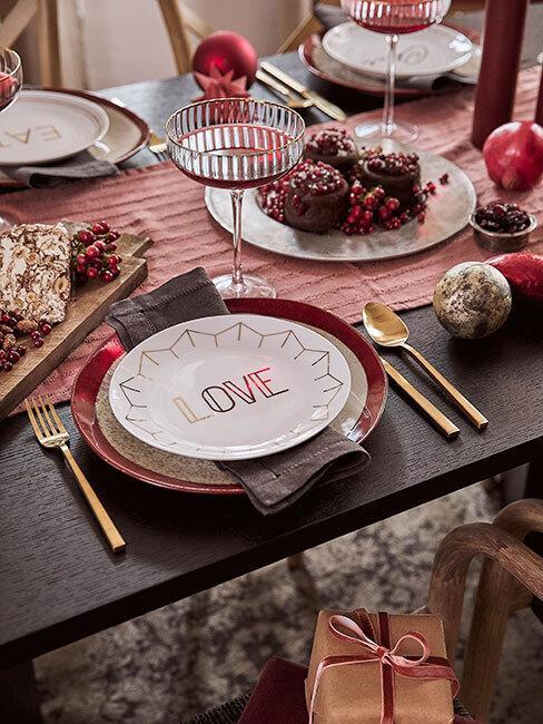 Czarny, drewniany stół nakryty czerwonym obrusem z białym talerzem z westwiing collection z napisem love oraz złote sztućce